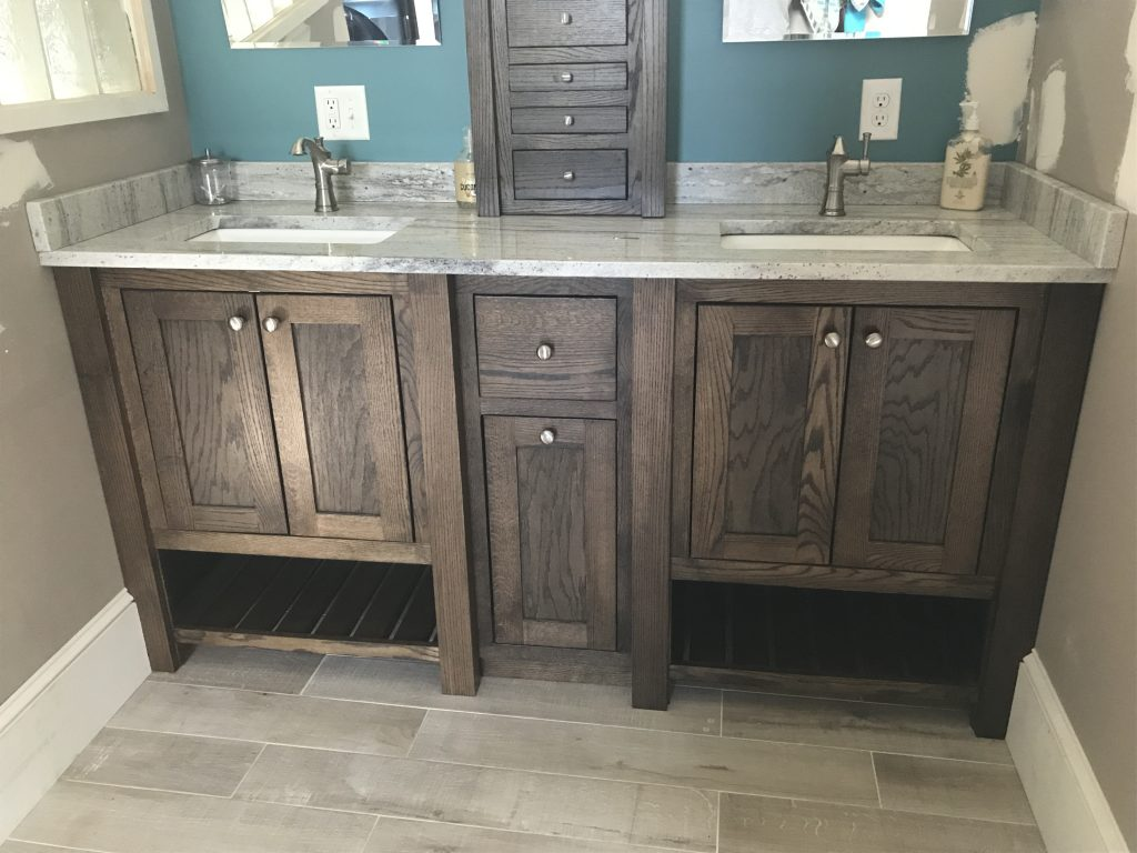 Completely built for the exact space, locally sourced Red oak vanity cabinets. Tower storage on top of the granite. 3 coats of matte finish poly over a dark walnut stain