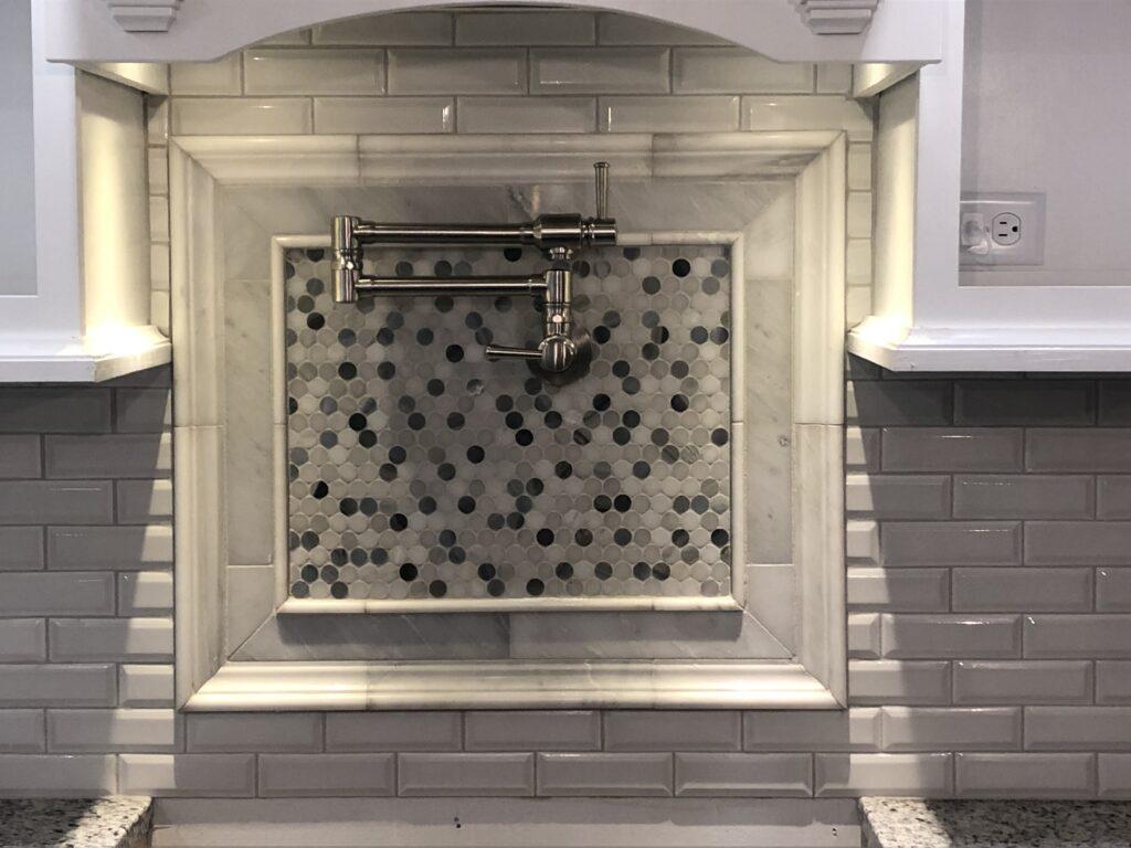 photo of custom tile backsplash with custom pot filler medallion