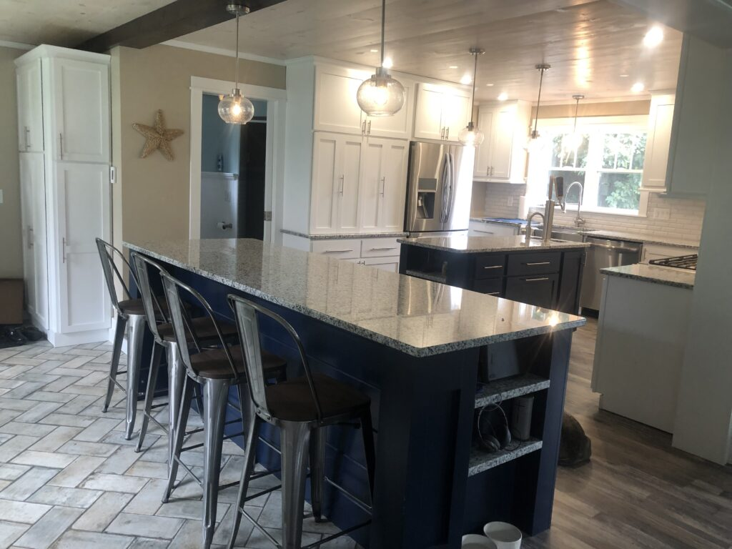 White and Navy, cabinets, custom made in our shop, twin islands, white washed pine ceiling , timber beam (actually steel covered to look like a timber)