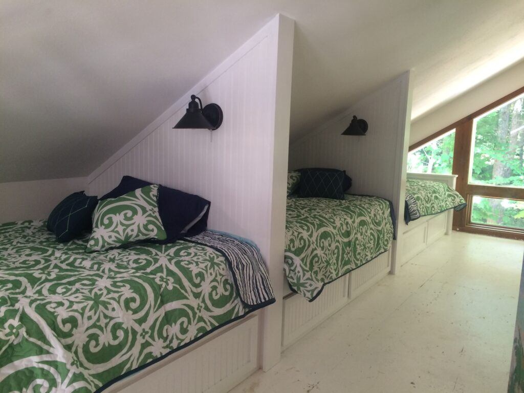 Triple set of bunks for the loft in a summer home. Built in storage underneath and a reading light for bedtime stories.