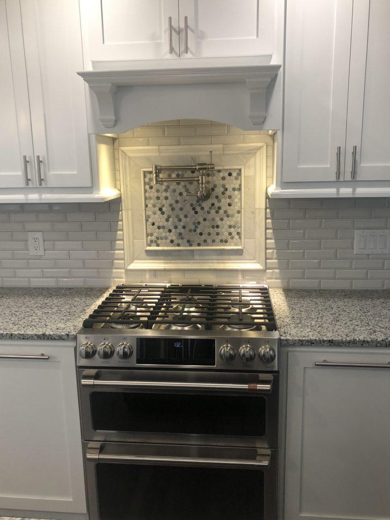 More 15 North custom, locally made cabinets, subway tile backsplash, custom pot filler, medallion tile over the gas range.