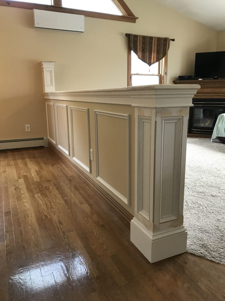 Half wall built to separate a living and dining space, custom wainscoting panels