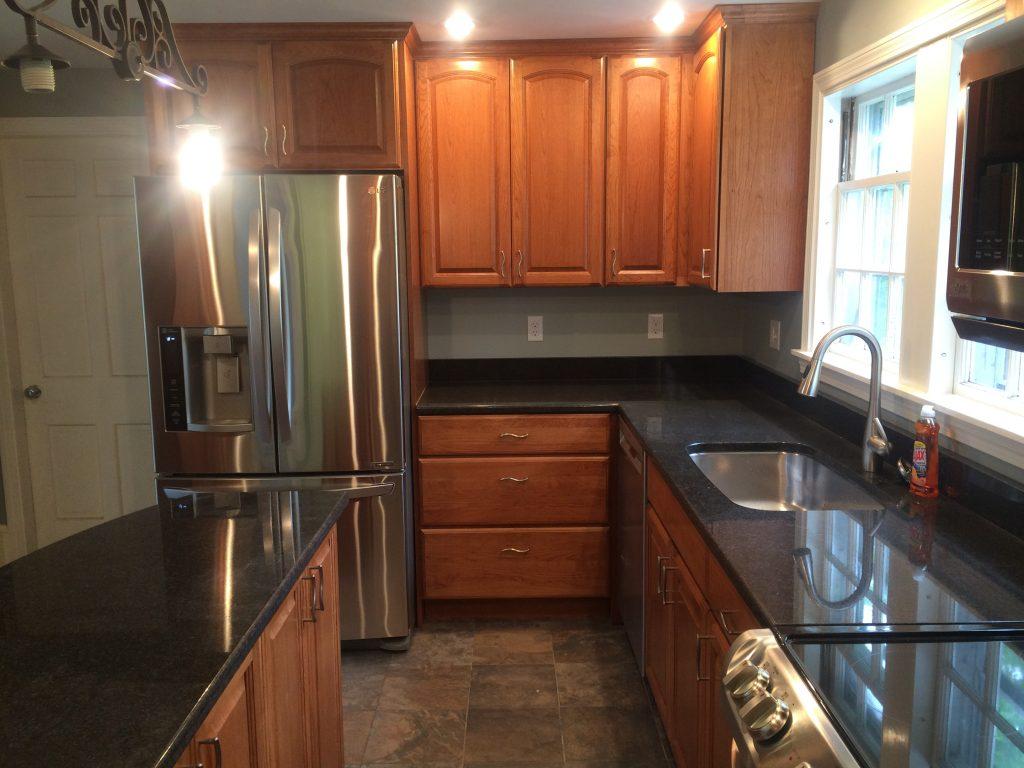 Cherry cabinets, black granite, tile floor