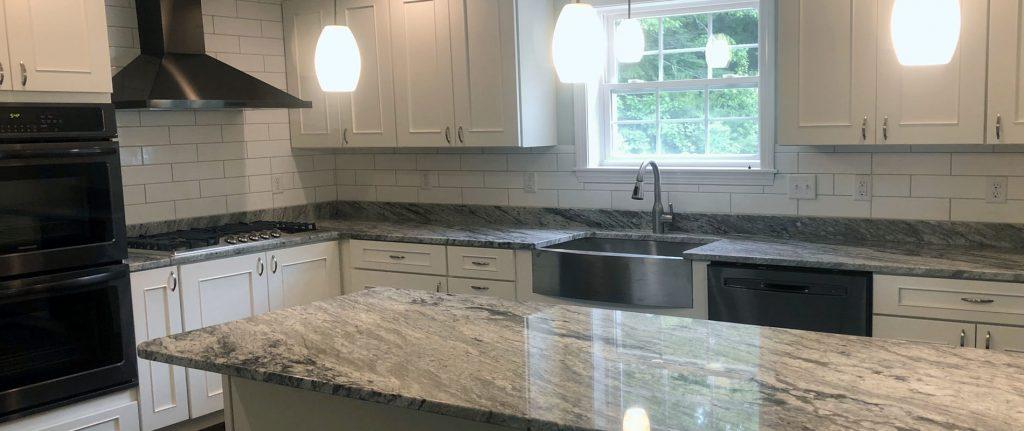 White Maple cabinets, subway tile backsplash, farmers sink, different granite on the island