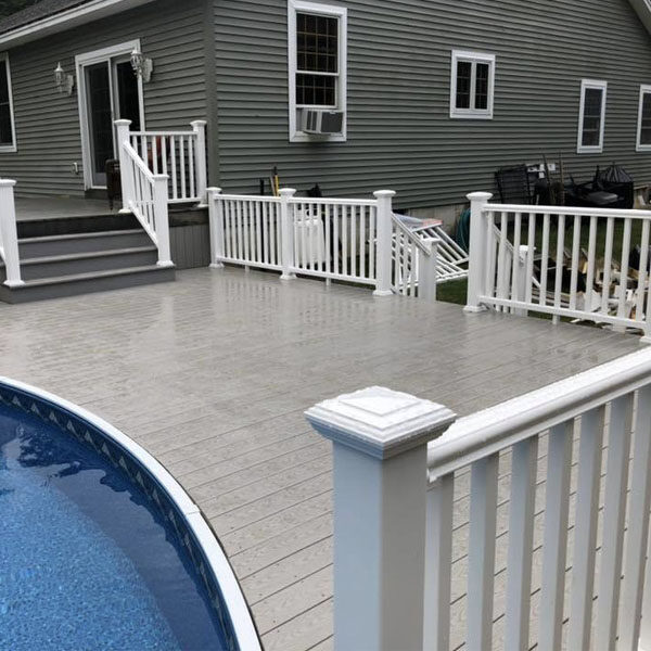 Non slip Composite decking and PVC rail nestled up against the pool.